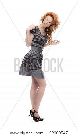 Fulllength shot of a redhead in a grey dress