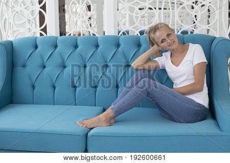 Young beautiful woman sitting on blue modern sofa