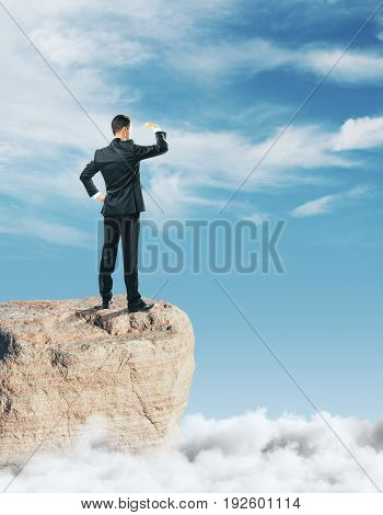 Businessman standing on rock and looking into the distance on sky background. Tomorrow concept