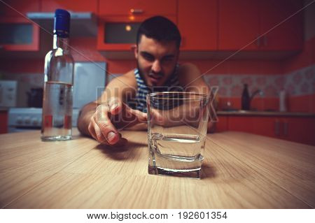 Alcohol addiction. Young man sitting at the table and drinking.