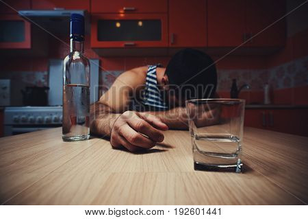Wide angle shot of young drunken man with bottle and glass lying on the table at home. Alcohol abuse.