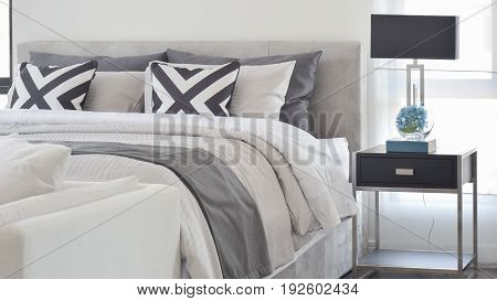 Modern Gray Tone Bedding And Bedside Table And Lamp In Black