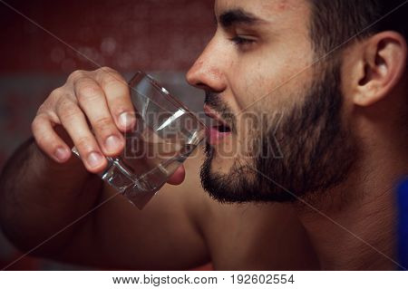 Closeup of male adult drinking alcohol. Alcohol addiction.