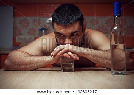 Depressed alcoholic man sitting at the table with glass and bottle of vodka. Alcohol addiction.