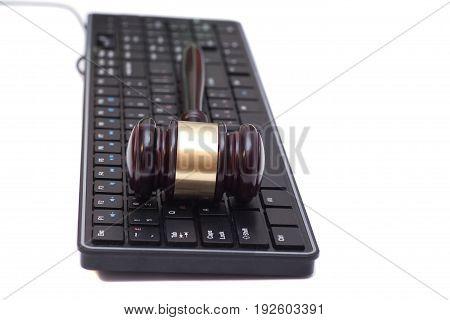 Judge gavel on black computer keyboard .
