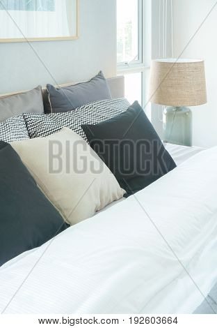 Modern Interior Bedroom With Pillows On Bed And Reading Lamp Next To Bed
