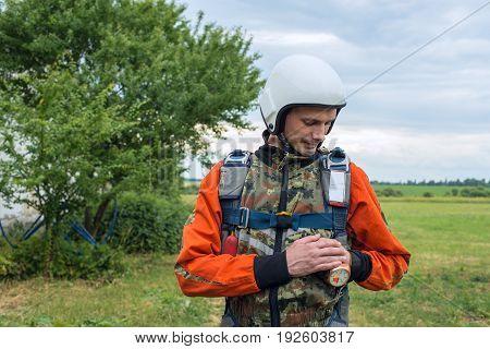 Portrait Of Resolute Skydiver Who Checks His Gear
