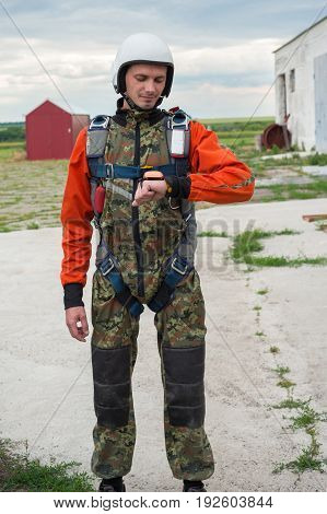Skydiver Stands On The Airfield And Checks His Gear
