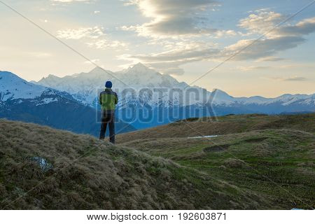 Lonely Traveler  Admires The Sunrise Over The Mountain Peaks