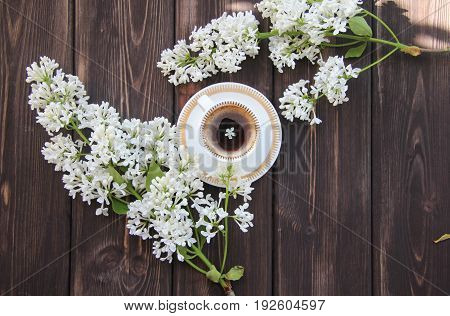 a Cup of a Cup of coffee and a branch of lilacs on a wooden tablecoffee and a branch of lilacs on a wooden table