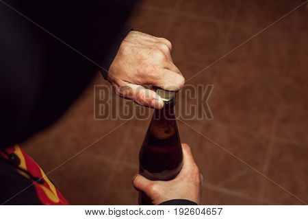 Closeup of male hands opening beer bottle. Alcohol addiction.