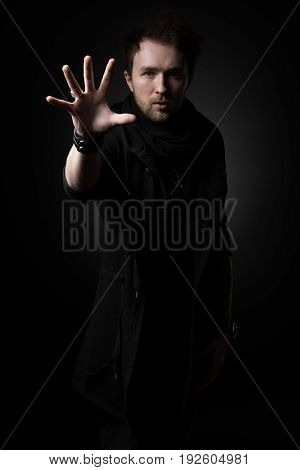Male illusionist in black clothes on a black background