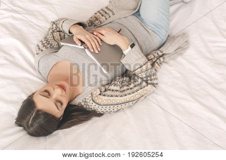 Young girl lie on bed with a book relaxation sleeping