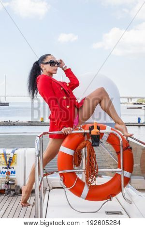Beautiful brunette woman in denim pants and jacket posing near the yacht port, yacht