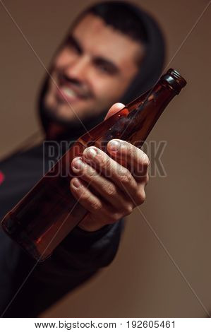 Young smiling man holding beer bottle in hands. Alcohol addiction
