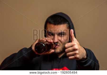 Portrait of young man drinking beer and showing thumbs up gesture. alcoholic addiction.