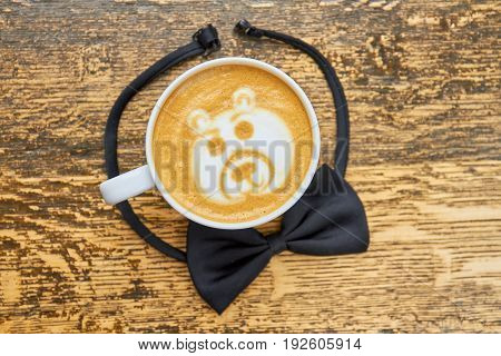 Black bow tie and coffee. Latte cup top view. Good morning gentlemen.