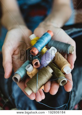 Handful of colorful skeins of thread in the hands of a woman