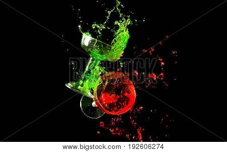 Clinking two glasses of red and green water splash on dark background.