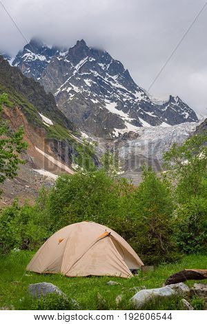 Tent Of Travelers Next To A Glacier In A Mountain Gorge