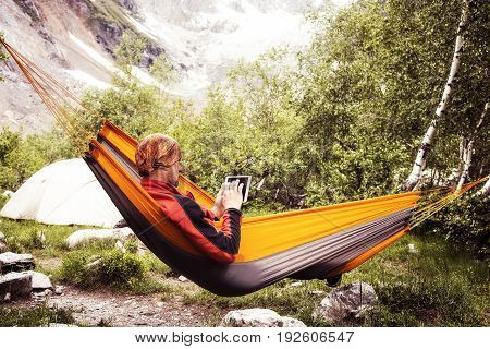 Traveler Relaxing In Hammock In The Mountains