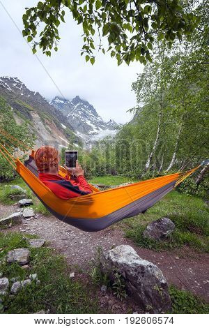 Adventurer Relaxing In Hammock In The Mountains, Takes A Photo Using A Tablet