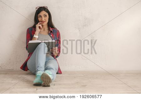 Young female thinking with a book isolated on white