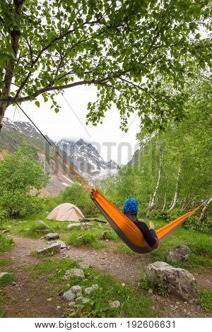 Woman Traveler Relaxing In Hammock, Next To Glacier
