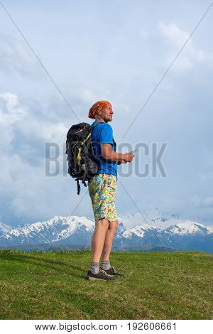 Traveler Is Walking Along The Ridge, Holding The Tablet In His Hands