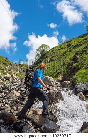 Man Adventurer With Backpack Is Preparing To Jump Over A Mountain River