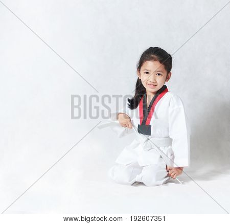 Happy Asian little girl smile sitting and tie a white line in taekwondo uniform on white background with copy space
