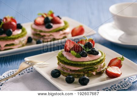 Homemade spinach cake with strawberry mousse .