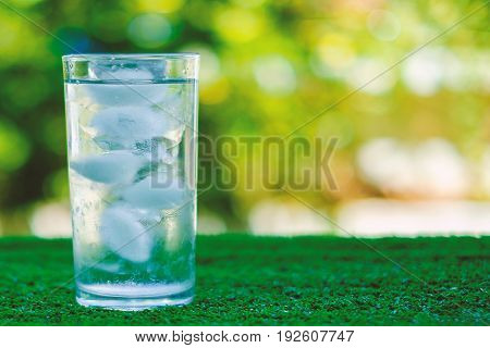 Cool water into a glass of ice with blurred natural green background and added color filter
