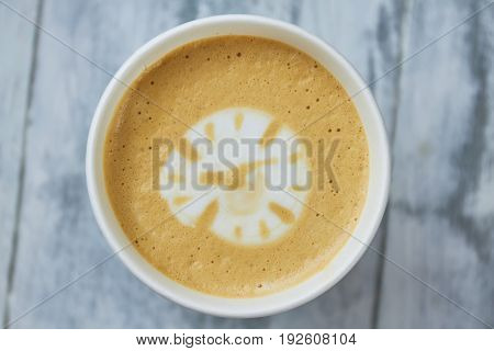 Latte art clock. Light coffee foam, top view. Does coffee boost productivity.