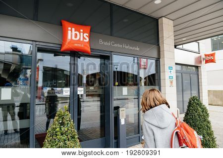 BRISTOL UNITED KINGDOM - MAR 8 2017: Woman entering the ibis hotel entrance welcome door with red signage and designed trees and red carpet - clean hotel with luxury entrance - Ibis Bristol Centre Harbourside