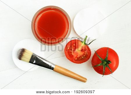 Tomato face mask for natural beauty care. Jar of juicy paste, red fresh fruit, applicator brush, top view white wooden background.