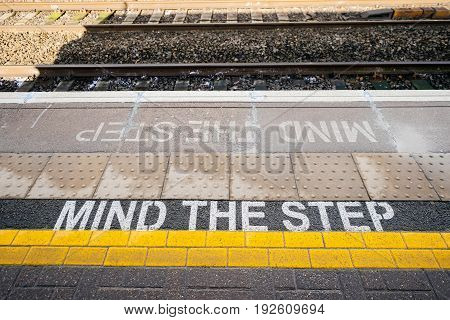 Directly above view of Mind the step yellow text line in British train station - visiting United kingdom taking care and security measures while traveling with train