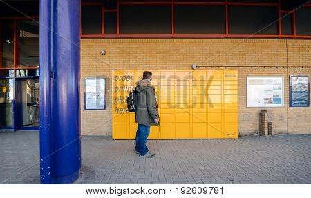 OXFORD UNITED KINGDOM - MAR 2 2017: Man looking at the Amazon locker orange delivery package locker train station - Amazon Locker is a self-service parcel delivery service offered by online retailer Amazon.com. Amazon customers can select any Locker locat