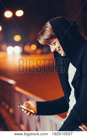 Handsome happy young man using smartphone while walking in night city streets. Smiling guy reading message outdoor