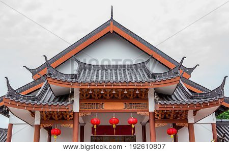 Traditional Chinese tile roof of wooden house decorated with oriental red lantern the Old Town of Lijiang China. Others black roofs and mountains are visible in background. Focus on the lantern