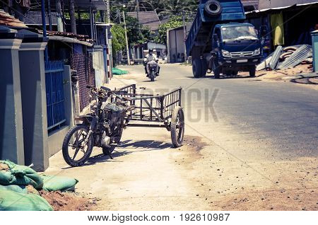 Motobike in the Vietnamese village adapted for cargo transportation. A picturesque village street. With toning