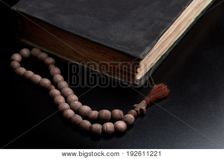 Old book and church rosary on a black background