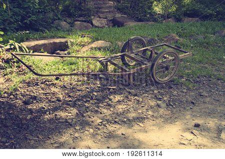 An old broken cart standing on a path. Asia. Vietnam. Toning.