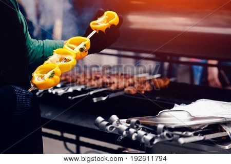 cook pushes the yellow pepper onto the skewer of the shish kebab, the vegetables are cooked on the grill. Concept dinner party, barbecue and roast pork