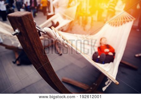 The tourist is resting in a hammock at the fair in the sunset. Concept harmony with yourself, urban vanity