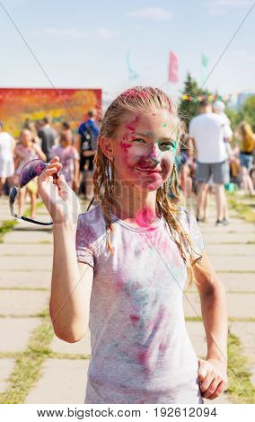 Joyful girl sprinkled with dry paint at the festival of paints