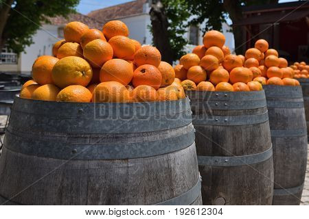Heap of bright ripe oranges at the barrels on the street of the medieval city of Obidos Portugal