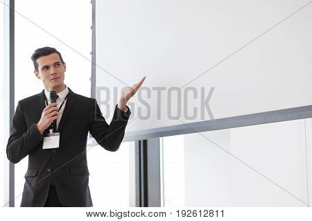 Businessman giving a presentation on blank white board with copy space