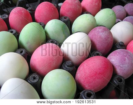 row of colorful eggs in the egg tray