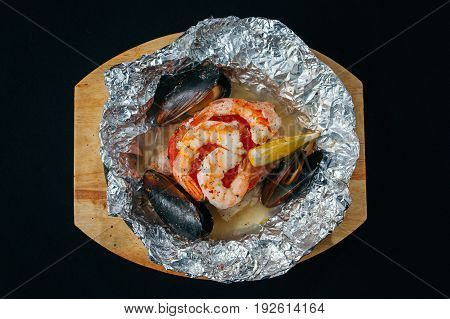 fresh oyster and shrimp on a white square plate. Black background.